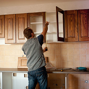 Man working on kitchen cabinets